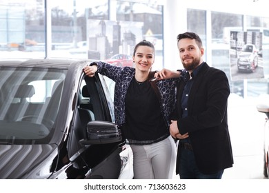couple chooses the new car in the showroom