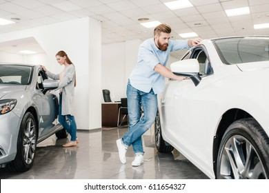 Couple choosing car, man and woman looking on various cars in dealership salon