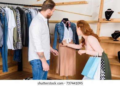couple choosing clothes on shopping in boutique