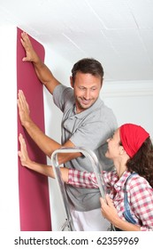 Couple choosing color of new wallpaper