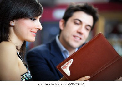 Couple choosing from a menu in a restaurant
