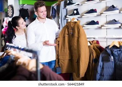 couple choosing new coat in sports store