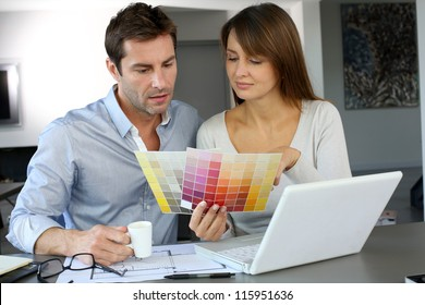 Couple choosing paint colour for their new home