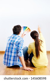 couple choosing paint swatch for new home