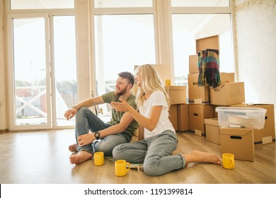 Couple Choosing wallpapper For New Home while sitting in bright room