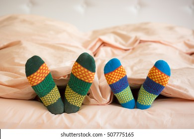 Couple in Christmas socks in bedroom. Man and woman lying on bed. People relaxing at home. Winter holiday Xmas and New Year concept