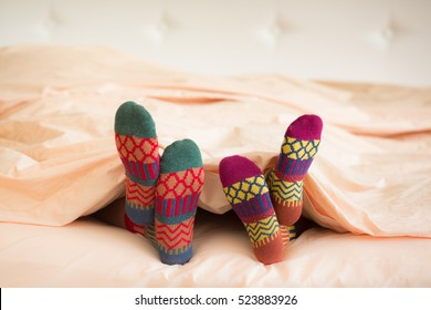 Couple in Christmas socks in bedroom. Man and woman lying on bed. People relaxing at home. Winter holiday Valentine Day and New Year concept