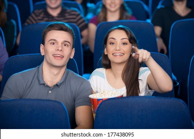 Couple at the cinema. Happy young couple eating popcorn and drinking soda while watching movie at the cinema
