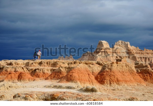 A couple climbing the red rock at Badlands, South Dakota, when storm is coming