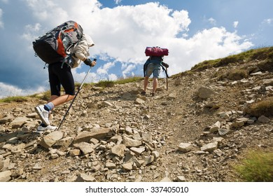 couple climbing uphill with backpacks