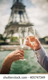 Couple cling the champagne glasses together under the Eiffel Tower in Paris, France.