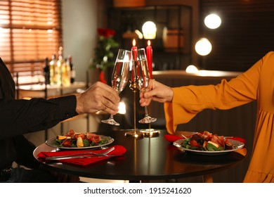 Couple clinking glasses of champagne at romantic dinner in restaurant, closeup