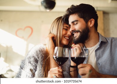 Couple clinking glasses with red wine. Couple celebrating anniversary, Valentine's day or International woman's day.