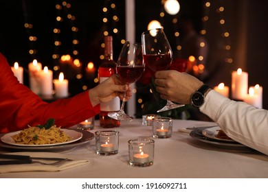 Couple clinking glasses of wine in restaurant, closeup. Romantic dinner