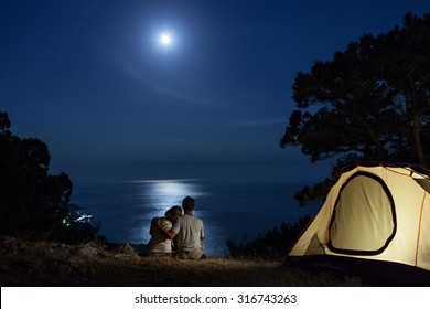 Couple close to tent looking at moon night above sea