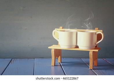 Couple coffee cups on old bench. vintage filtered. Romance and weekend concept