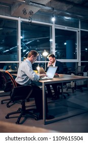 Couple of colleagues sitting at office table with laptops. Two serious businessmen working in middle of night in their modern office with glass windows.