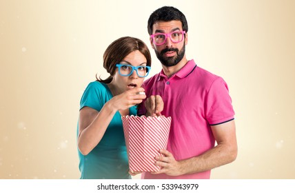 Couple in colorful clothes eating popcorns on ocher background