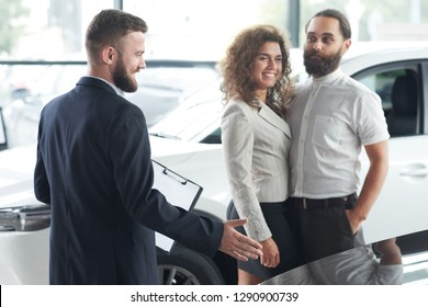 Couple communicating with manager in car dealership. Car dealer wearing in dark blue jacket showing with hand vehicles. Beautiful woman and bearded man observing automobiles.