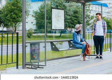 Couple communicating while waiting at bus stop. Hansome man and elegant woman with backpacks meets and talks at tram stop, outdoor. Students waiting for tram. Full height.