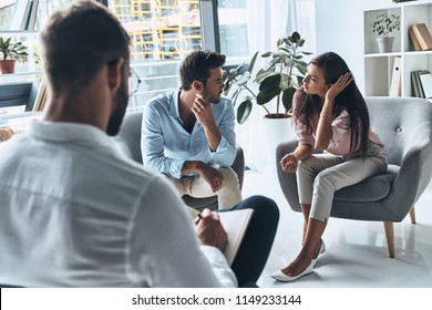 Couple in conflict. Young married couple talking while sitting on the therapy session with psychologist