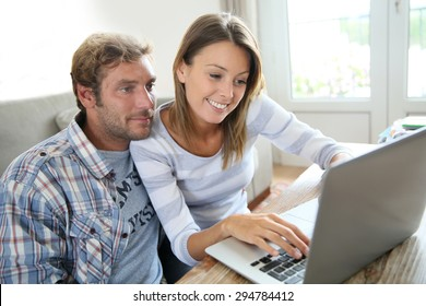 Couple connected on internet with laptop computer at home