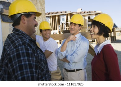 Couple at construction site talking to workers