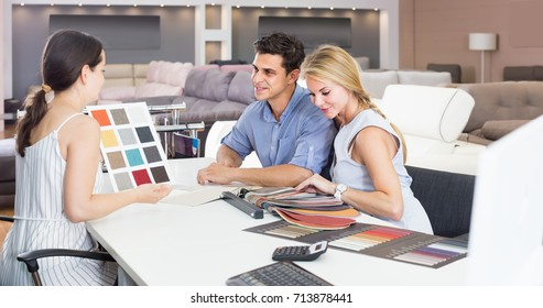 couple are consulting with seller about the colors of furniture in furniture store