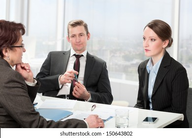 couple consults with a mature woman lawyer, signing paperwork