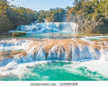 Couple contemplating the majestic turquoise waterfalls at Agua Azul in Chiapas, Mexico