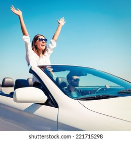 Couple in convertible. Happy young couple enjoying road trip in their convertible while woman raising arms and smiling