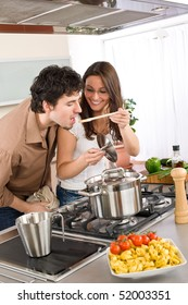 Couple cook in modern kitchen - man taste food