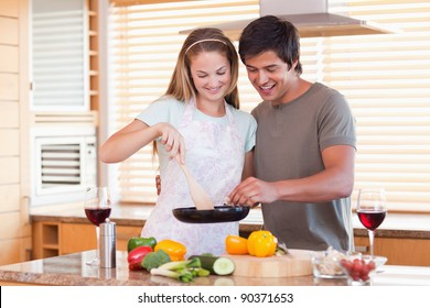 Couple cooking dinner while drinking red wine in their kitchen
