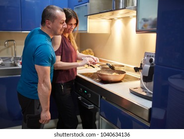 Couple cooking at home with pans on the stove