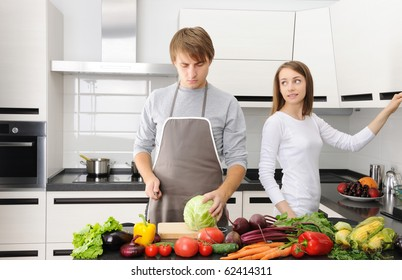 Couple cooking in modern kitchen, man chopping and cutting with knife