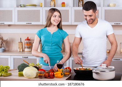 Couple cooking together. Happy young couple cooking together in the kitchen