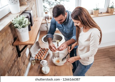 Couple cooking together at home. High angle image.