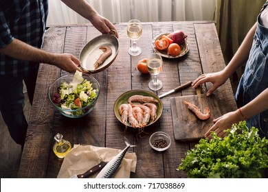 Couple cooking together shrimp dinner and salad of vegetables on a wooden table in home kitchen