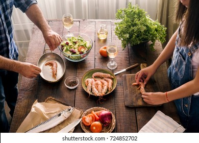 Couple cooking together shrimp dinner and vegetables salad on wooden table in home kitchen, top view