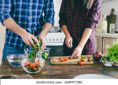 Couple cooking together summer salad of vegetables on wooden table in home kitchen