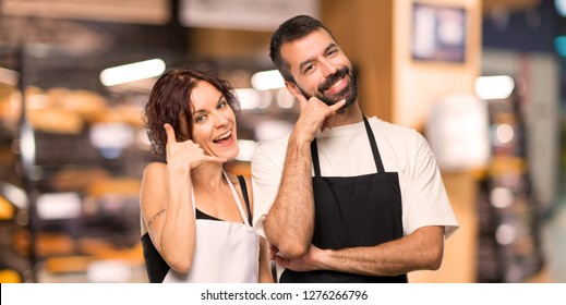 Couple of cooks making phone gesture. Call me back sign