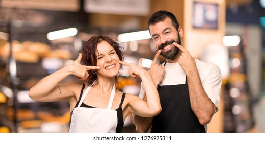Couple of cooks smiling with a pleasant expression while pointing mouth with fingers