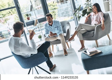 Couple counseling. Young married couple talking while sitting on the therapy session with psychologist
