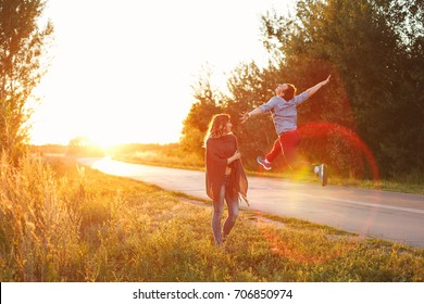 A couple at a country road. He jumps up cheerfully. She looks at him. They are fooling around. The road goes into the sunset. Love and tenderness.