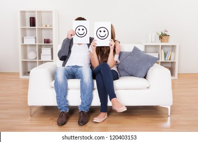 Couple covered faces with smiley white paper.