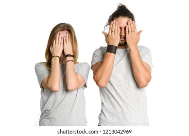 Couple covered their eyes. Man and a woman put their hands over their eyes together on white background. Close your eyes.