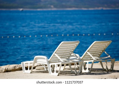 Couple of cozy white sun beds on the seaside.Travel destination background.Comfortable plastic lounge chairs for sunbathing and relaxation during summer vacation cruise.Relax and chill on sunbed