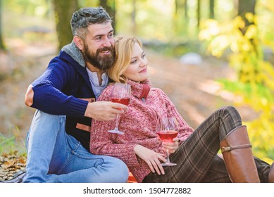 Couple cuddling drinking wine. Enjoying their perfect date. Happy loving couple relaxing in park together. Romantic picnic with wine in forest. Couple in love celebrate anniversary picnic date.