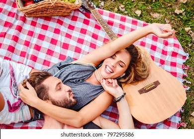 couple cuddling on a picnic blanket. She is listening music and he is sending her kisses