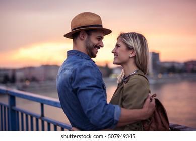 Couple cuddling while enjoying beautiful sunset together.